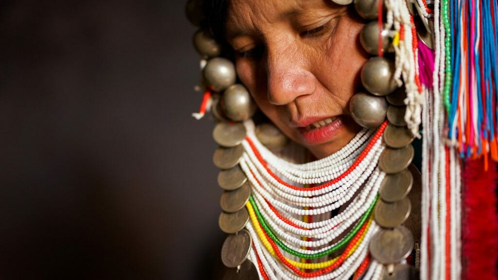 Close up of tribal woman wearing an elaborate headress of colourful beads and coins.