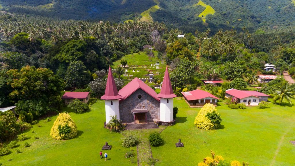 Red roofed church set amidst lush scenery.