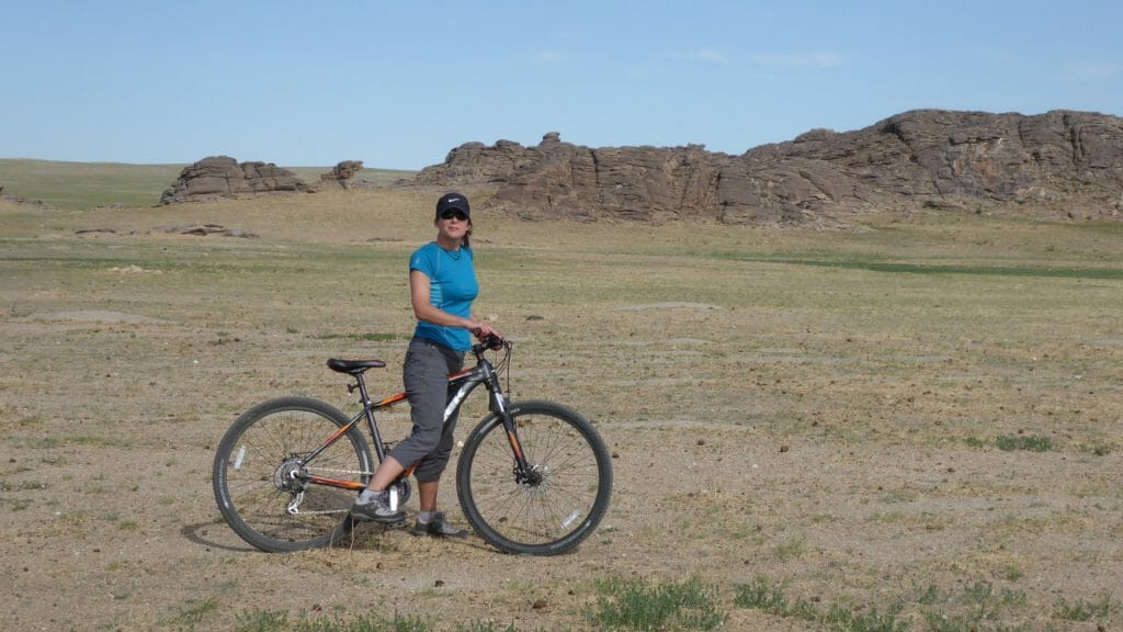 Lone cyclist on grass steppes of Mongolia.