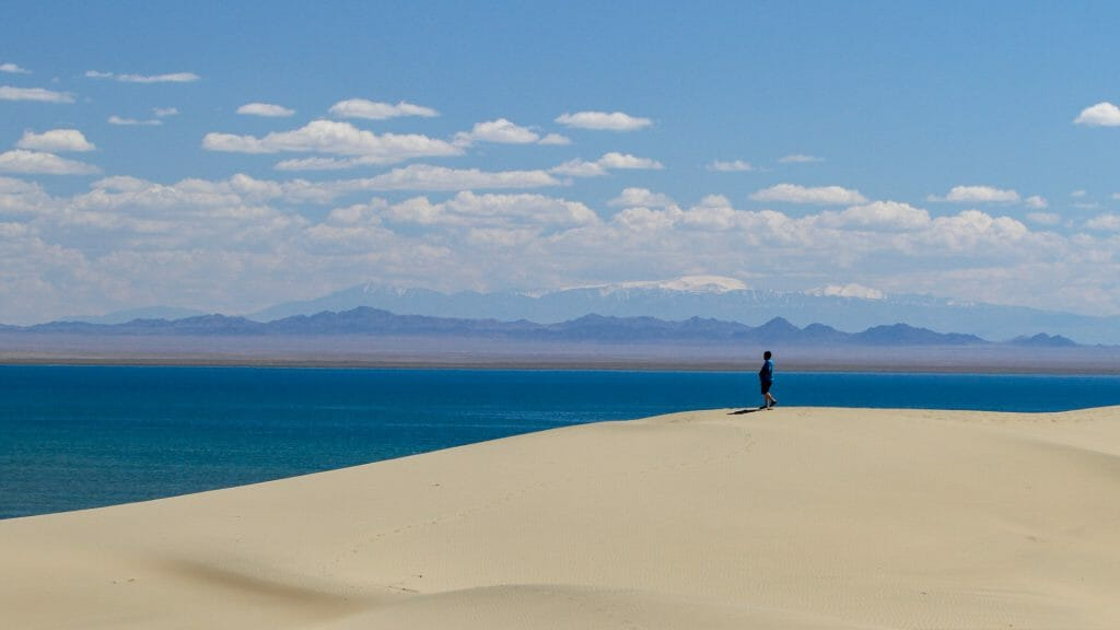Solitary figure on the crest of a sand dune with a vast blue lake behind and snow capped peaks in the distance.