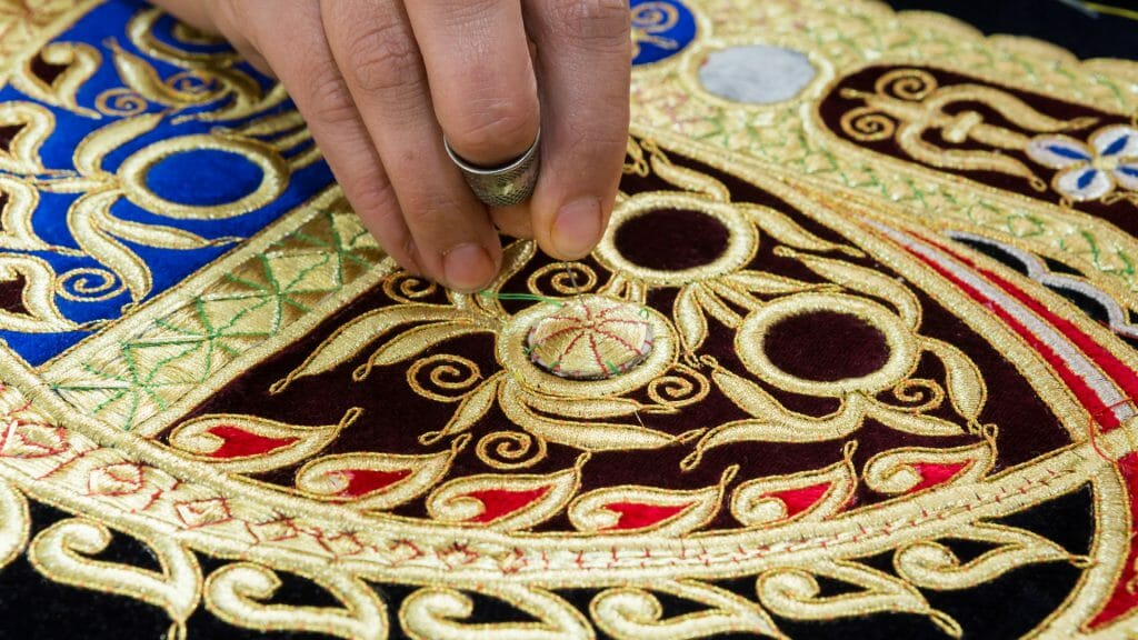 Close up of woman's hand embroidering with gold silk.