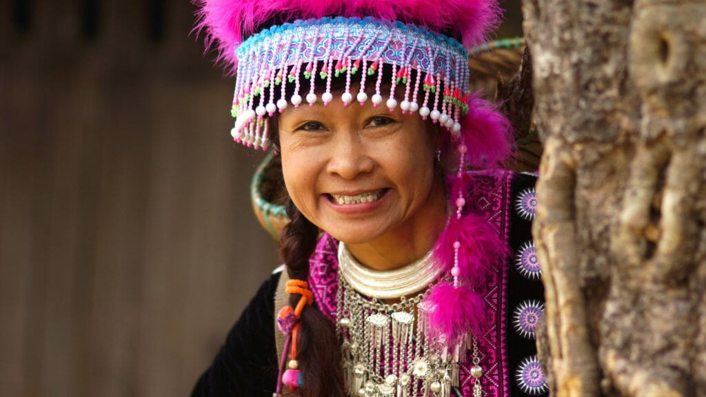 Portrait of hill tribe woman wearing colourful beaded and pink feathered headwear.