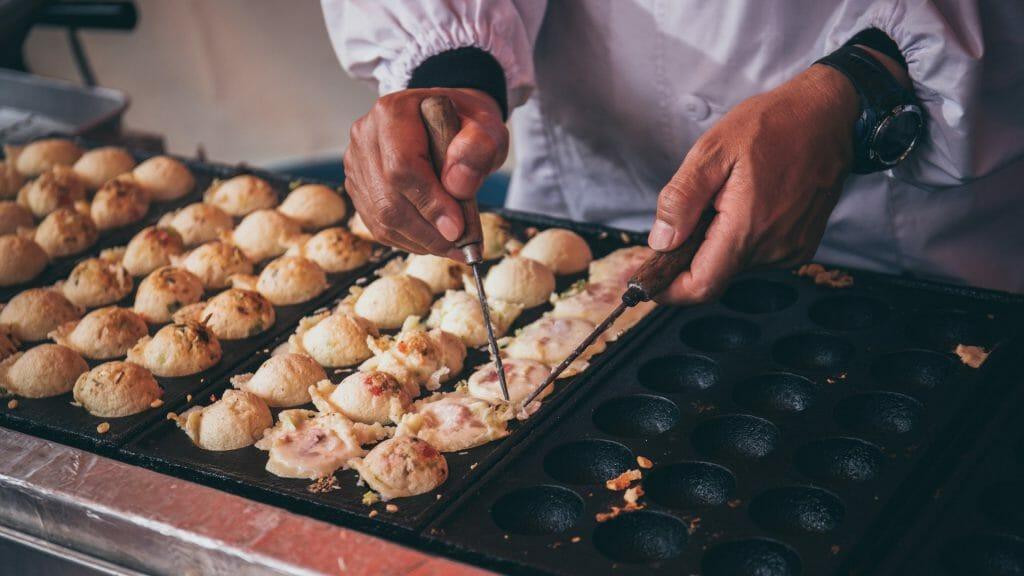 Mans hands preparing Japanese snack food.