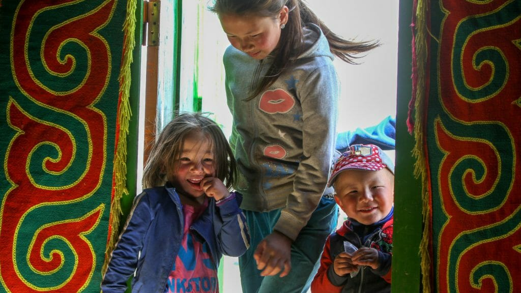 Three Mongolian children in brightly coloured ger doorway.