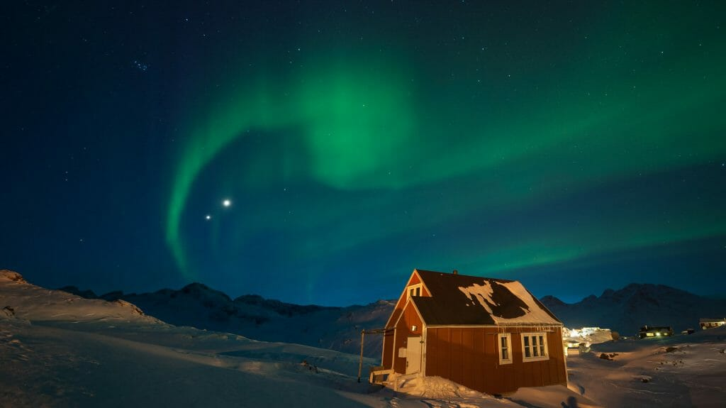 northern lights over a traditional wooden house, Greenland