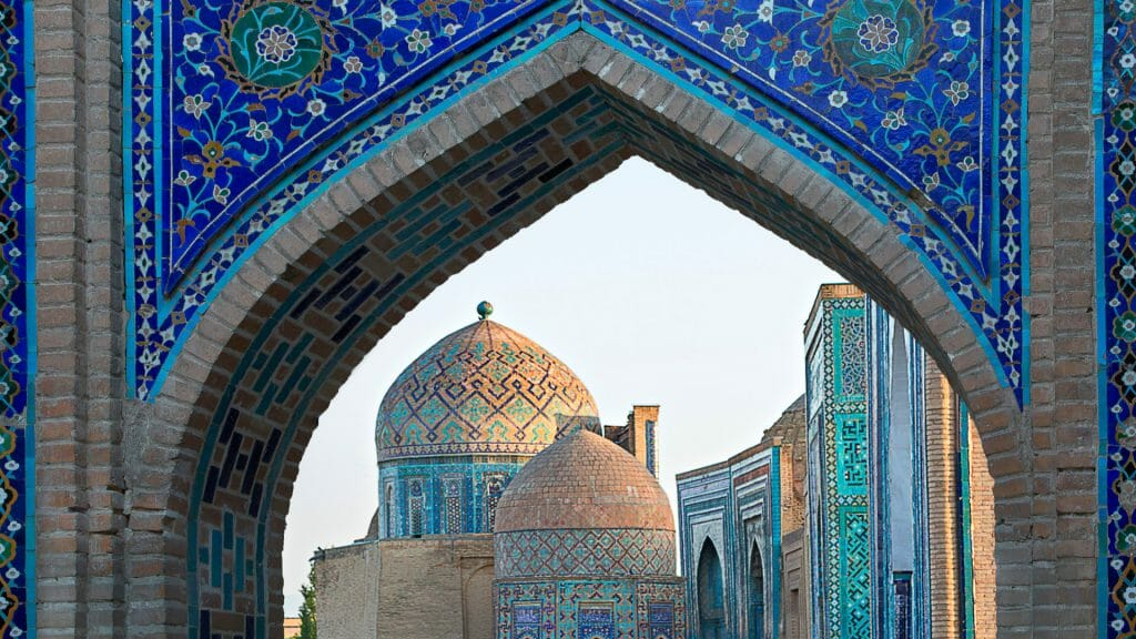 View of Islamic buildings through blue mosaic archway.