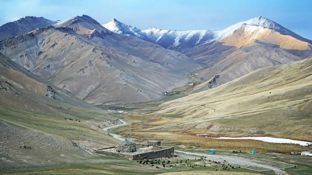 Wide panoramic view valley with caravanserai at the base and snowy peaks in distance.