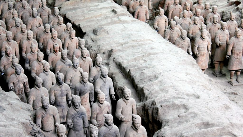 Lines of terracotta warriors stood in tomb trenches.