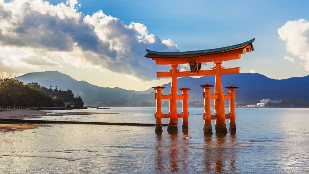 Traditional Japanese red gate in the ocean against a mountain backdrop.