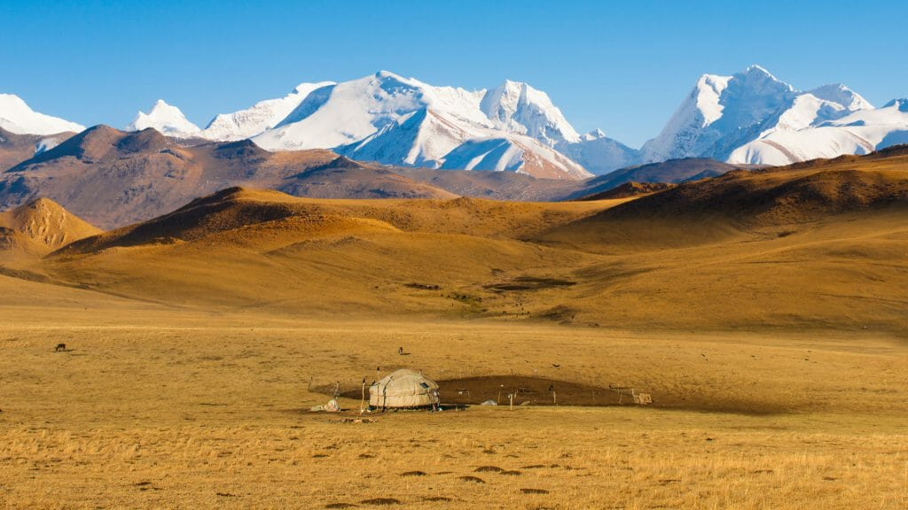 Traditional yurt on open steppes with snow capped mountains in the background.