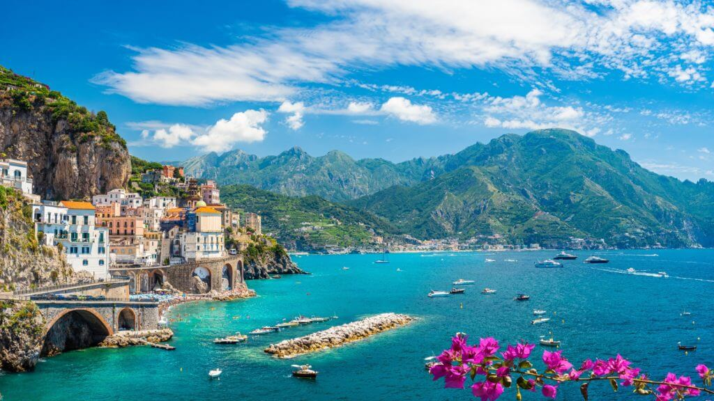 The ancient cliffside town of Atrani overlooks sail boats on turquoise blue ocean on Italy's Amalfi Coast
