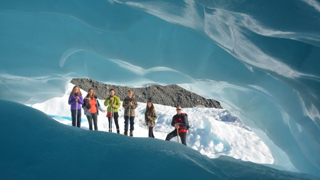 Vibrant blue ice with view through carved hole to six people standing on ice.