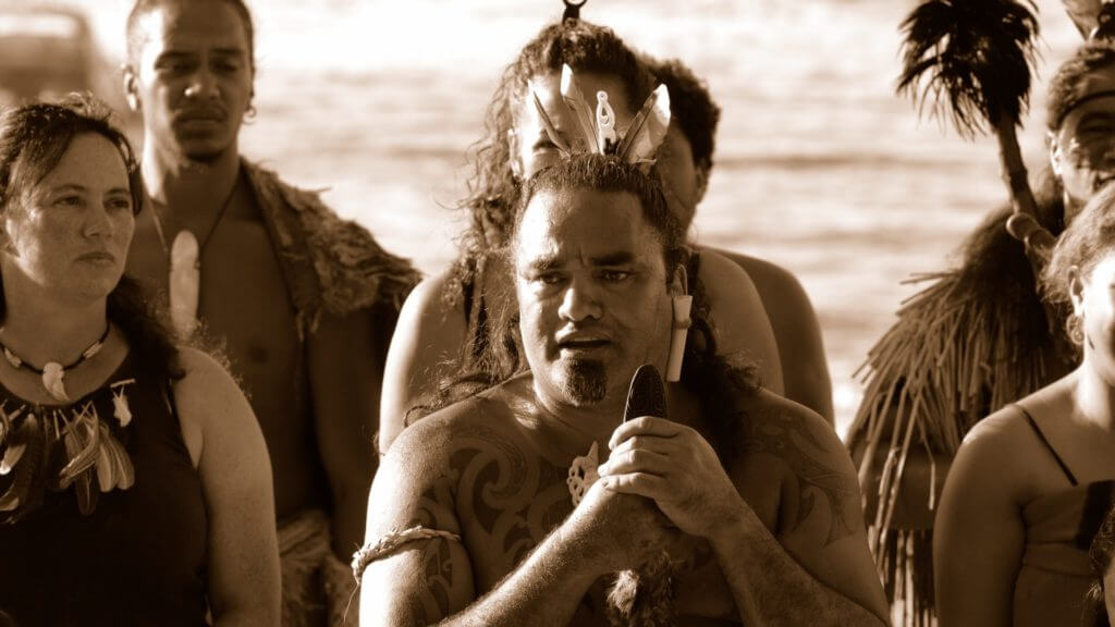 Black and white image of Maori people with tatoos, traditional jewellery and feathers in hair.