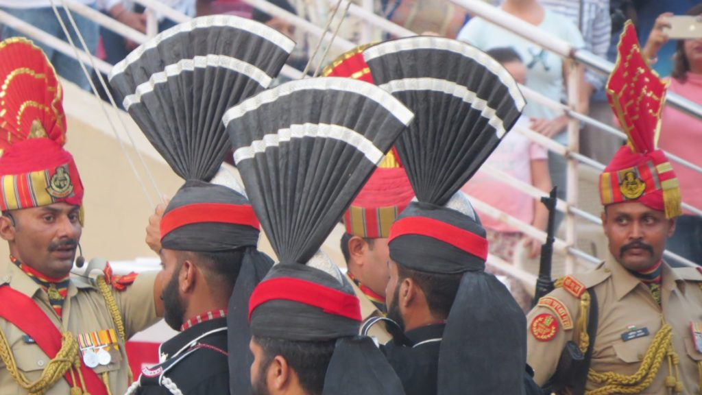 Black and white fan headwear of Pakistani guards marching.