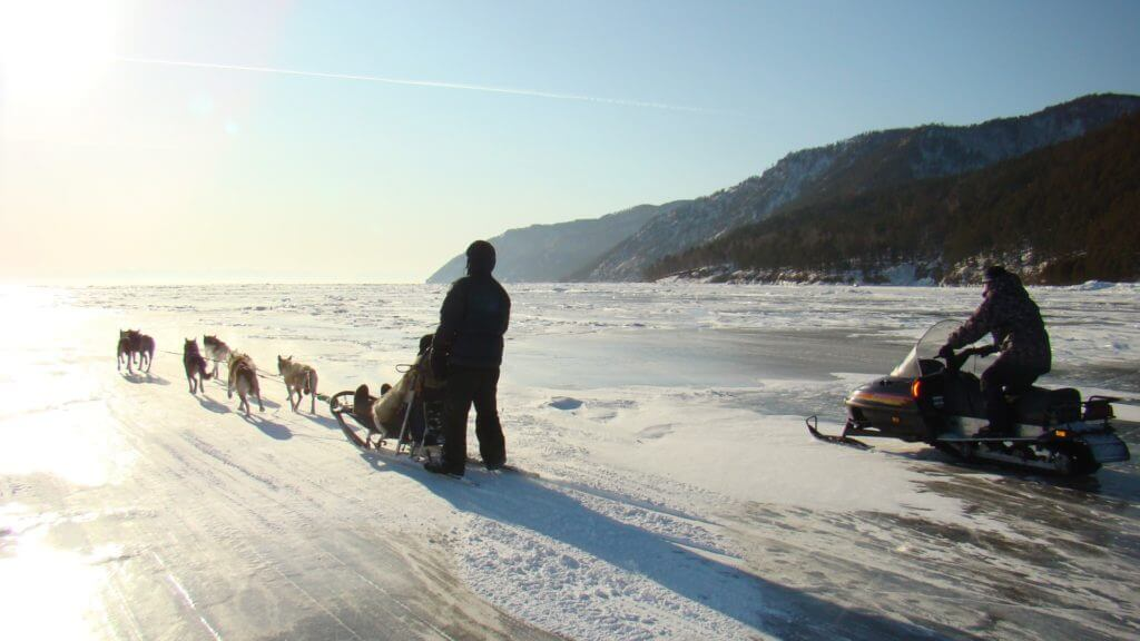Frozen lake Baikal with dog slegde and snowmobile silhouetted.