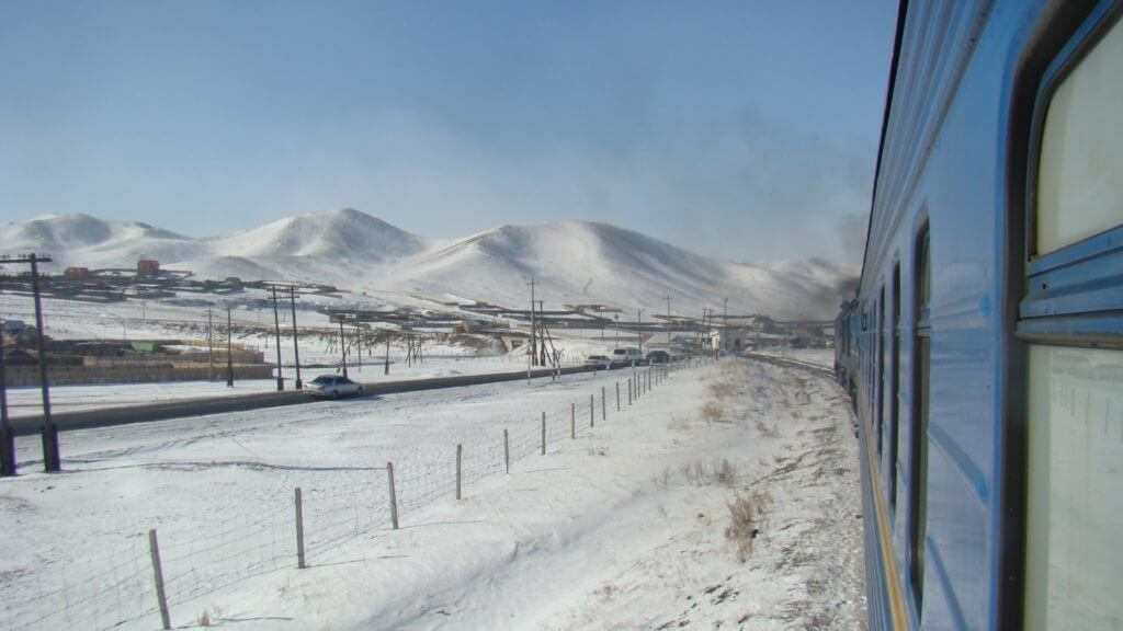 Side of a train travelling through snowy landscapes with snow covered hills in background.