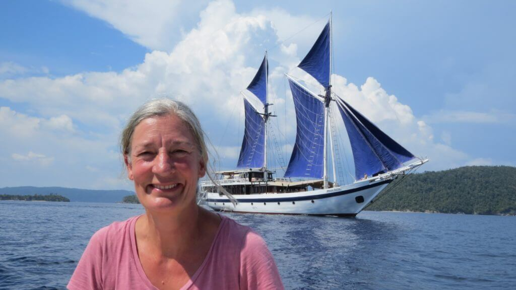 Steppes Travel staff member on the water with blue sailed Seatrek yacht in background.