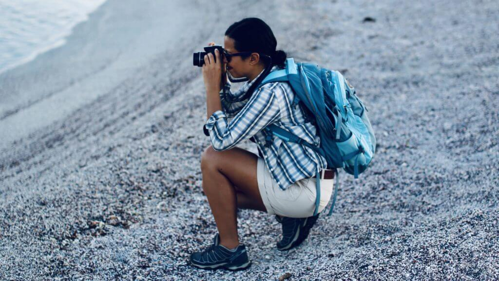 TV presenter and wild animal biologist Liz Bonnin taking photographs from a beach in the Galapagos Islands