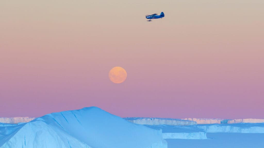 Small plane flying at sunset over Antarctica