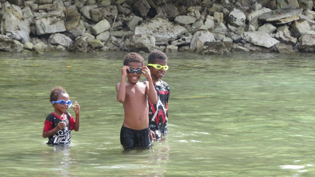 Three Indonesian village boys stook in water wearing newly gifted snorkels and big smiles.
