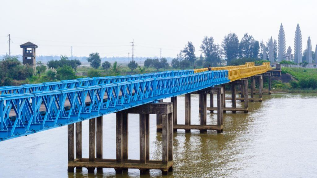 View of blue and yellow iron bridge over river.