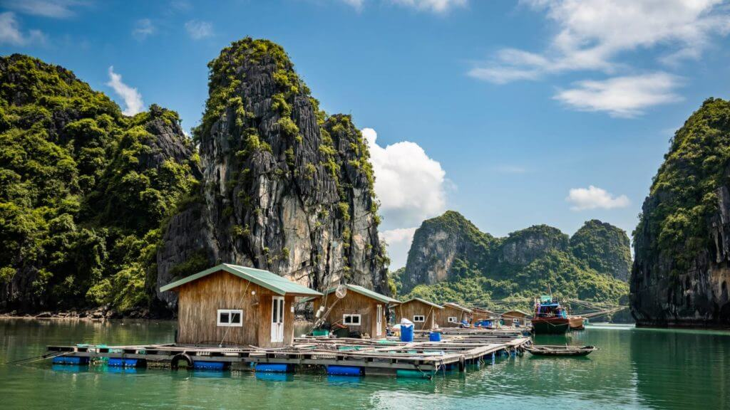 Row of small wooden cabins on floating pontoons surrounded by karst limstone peaks.