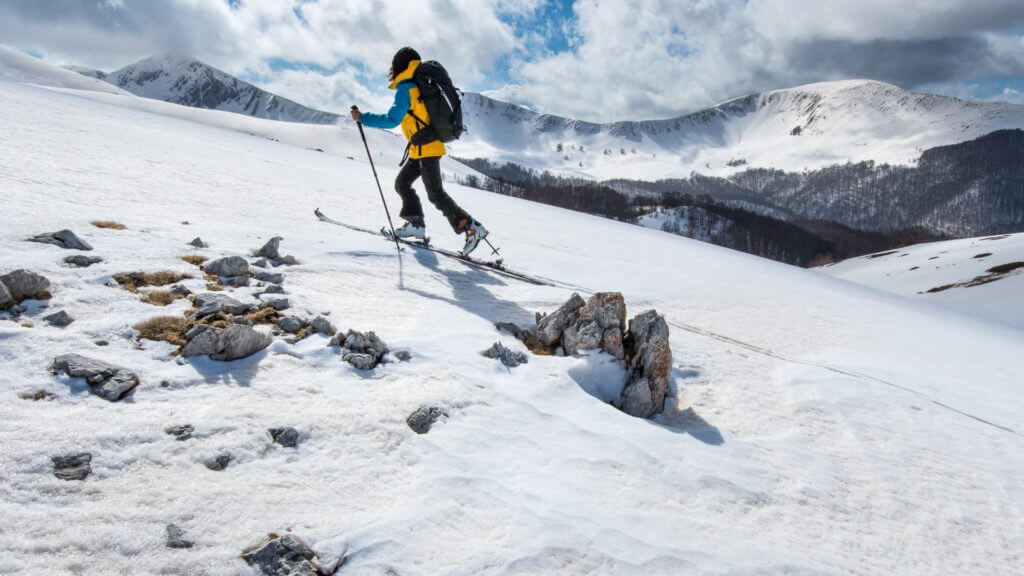 Side view of cross country skier in yellow coat, skiing up snow covered slope.