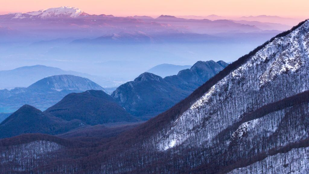 View of snowy mountains against picky, orange sky.