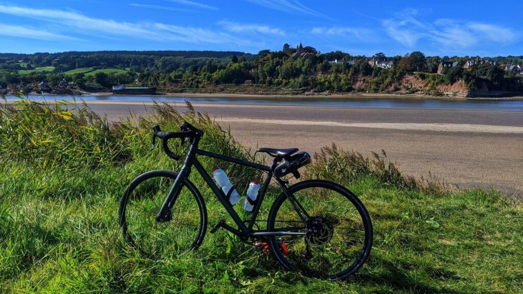 Cycling by river, Gloucestershire, England, UK