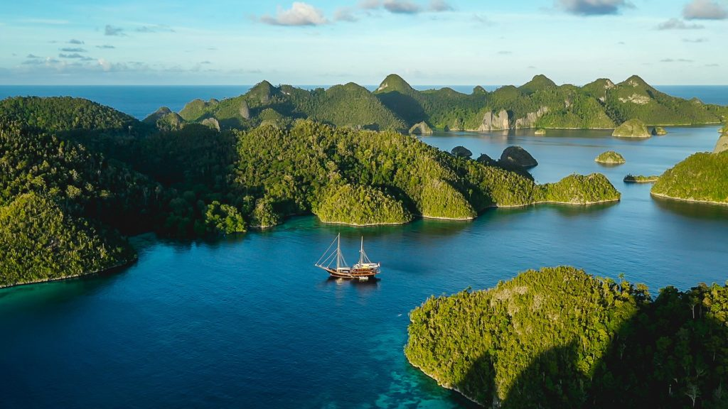 Aerial view of yacht on water amidst rainforest covered inlets and islands.