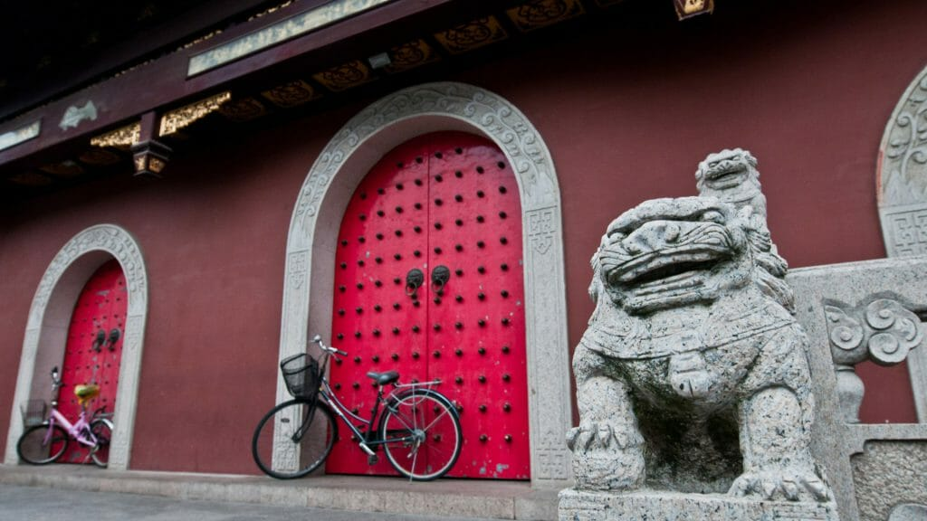 Red wall, red arched doors with bike against and stone carved lion in foreground.