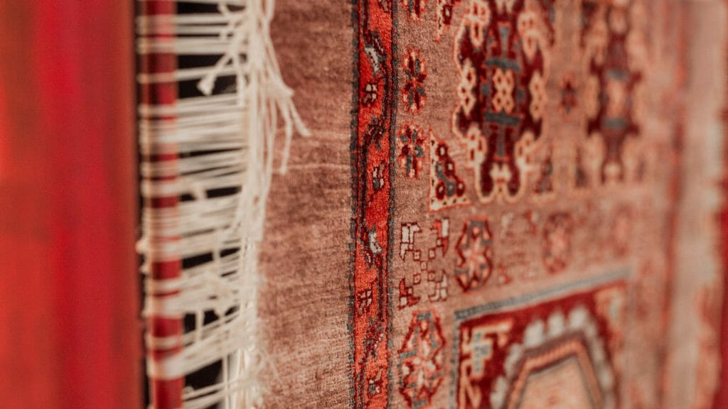 Full frame close up of patterned red carpet.