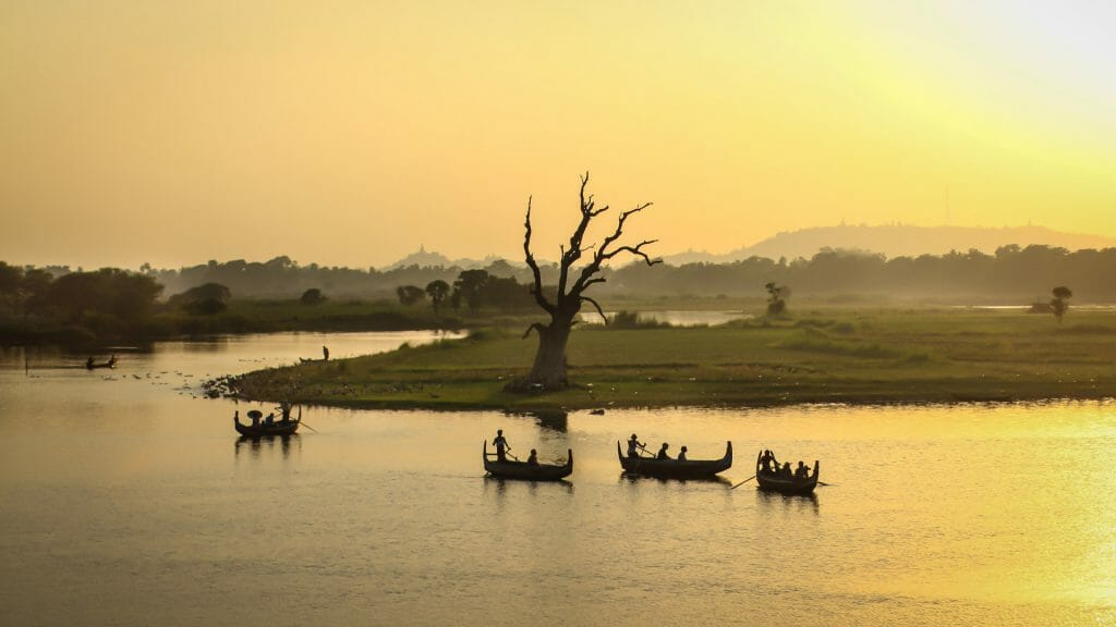 River at sunset with silhouettes of four traditional boats against yellow sky.