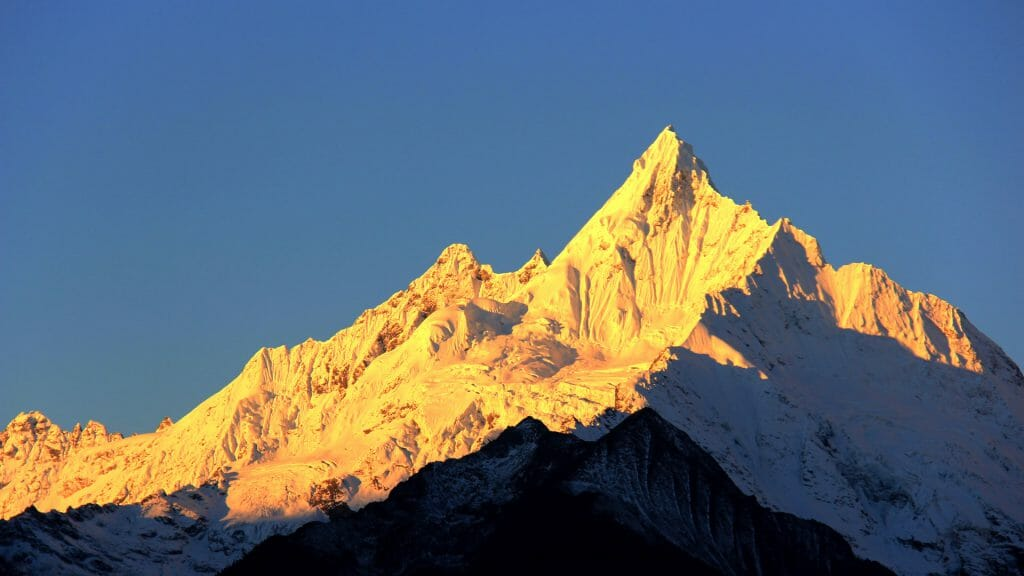 Snow covered peak of jagged mountain against bright blue sky.