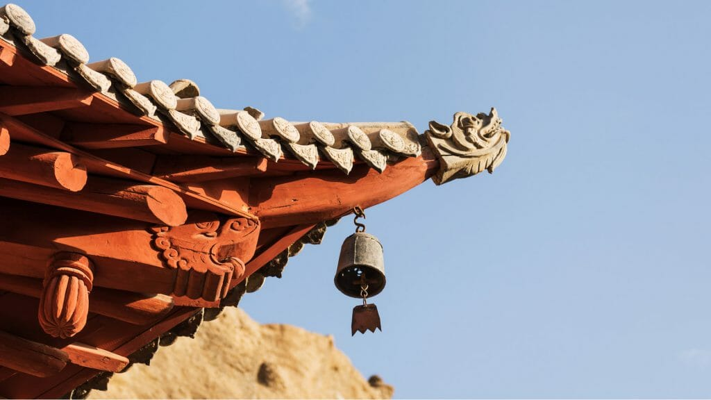 Corner of a traditional Chinese rooftop against blue sky.