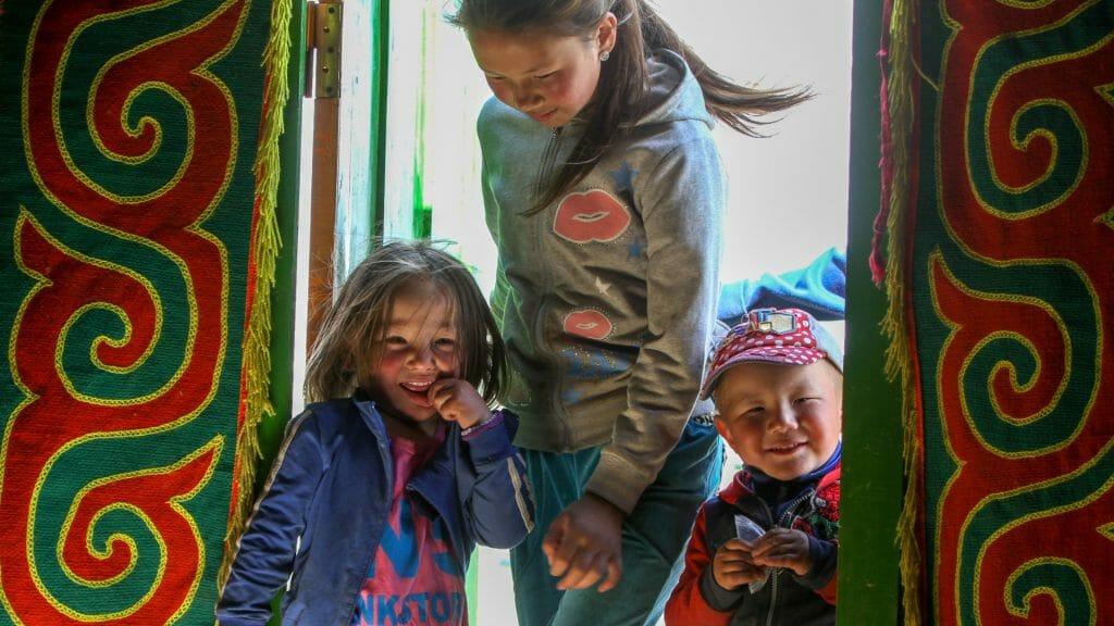 Three Mongolian children in brightly coloured ger doorway.