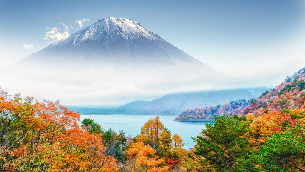 Autumnal foliage with lake and misty snow capped mount fuji beyond.