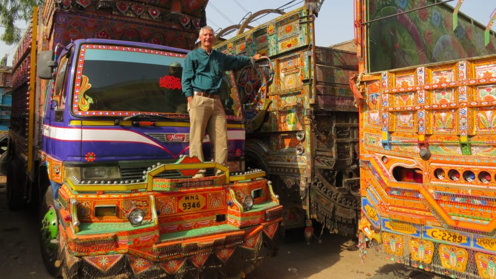Paul stood on the bonnet of a brightly coloured, decorated Bedford truck.