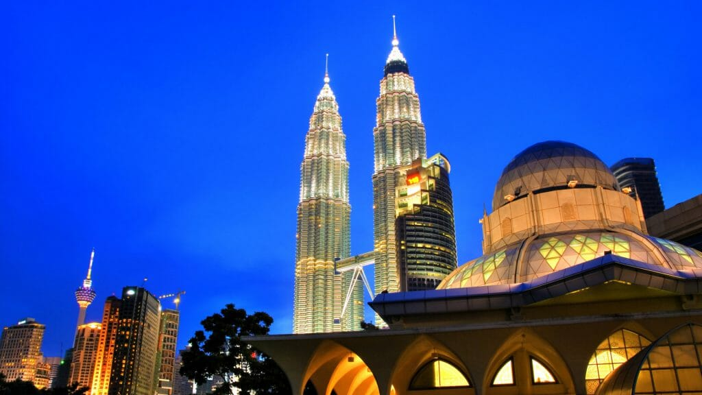 Looking up at Petronas Towers lit up at night.