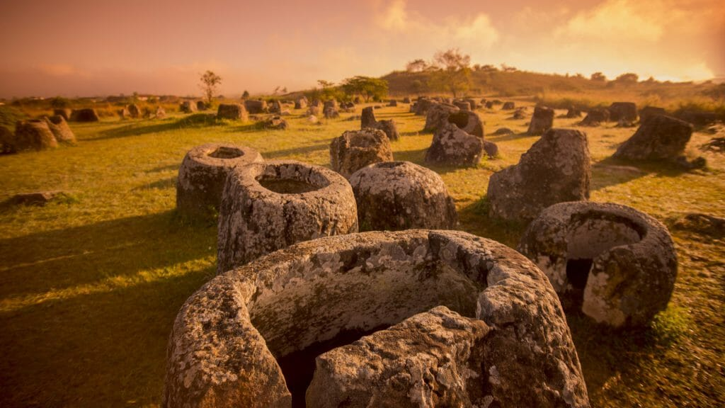 View of ancient jar shaped rocks covering a plain at sunrise.