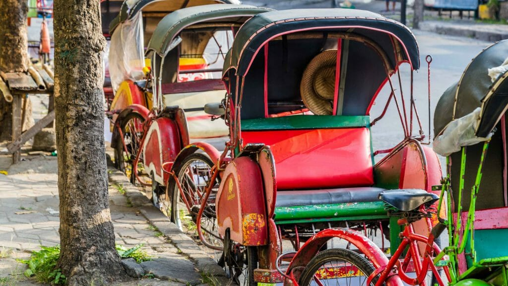 Traditional red and green rickshaws lined up along the kerbside.