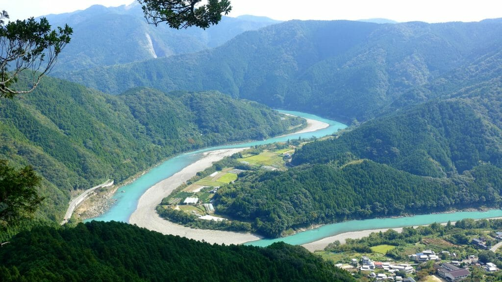 Panoramic aerial view of bending river weaving through lush hills.