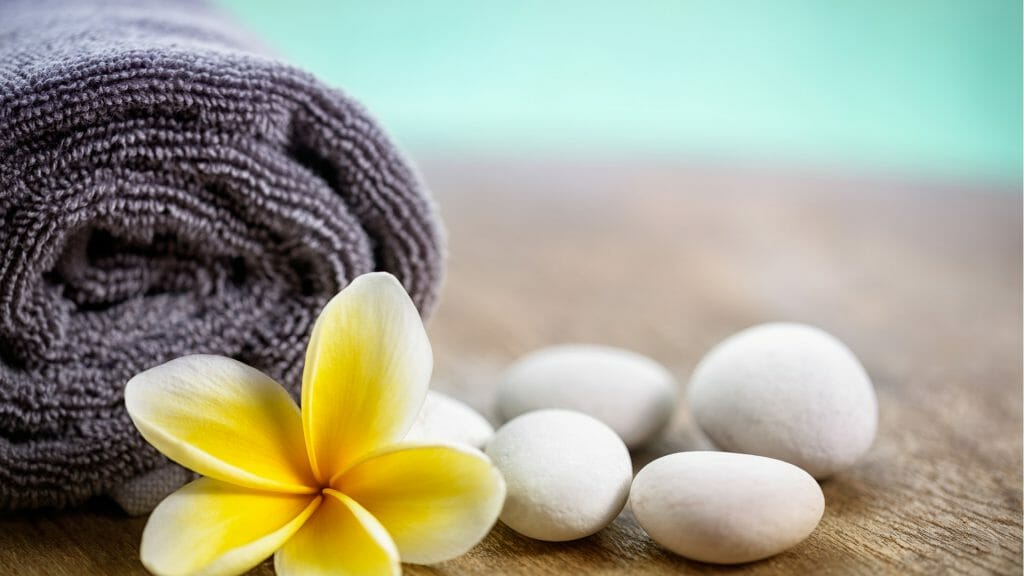 Rolled grey towel with a yellow frangipani flower infront of it and four white stones to one side.