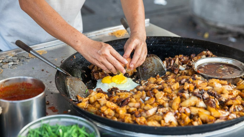 Large pan of food being cooked in a market.