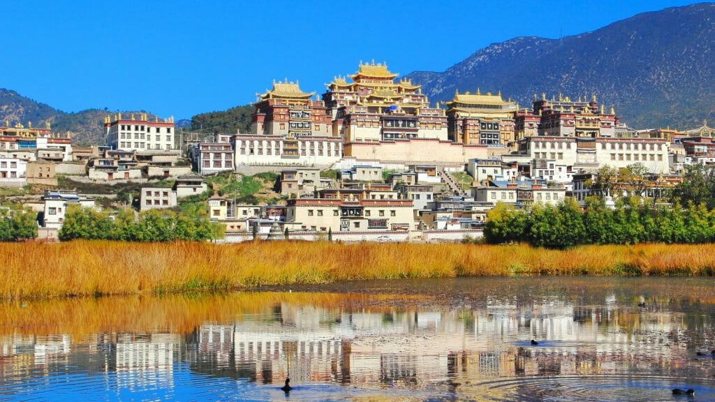 Tibetan Monastery town against blue sky, reflected in river.