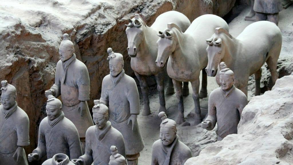 Terracotta soldiers and horses in a trench.