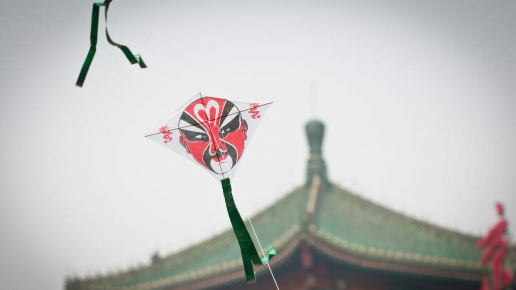 Traditional Chinese kite with Beijing opera face, Chinese rooftop in background.