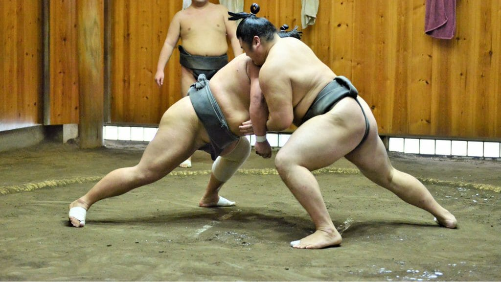 Two sumo wrestlers fighting.