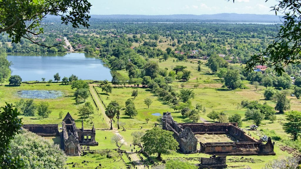 Aerial view of temple complex amid lush landscape.