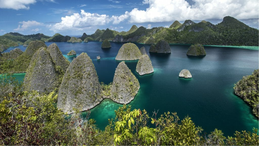 View of Raja Ampat with limestone island peaks, lush hills and ocean.